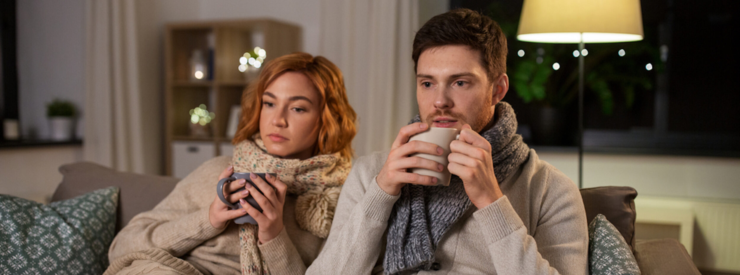 A Couple Sitting On A Couch, Under Blankets, Sipping A Hot Drink