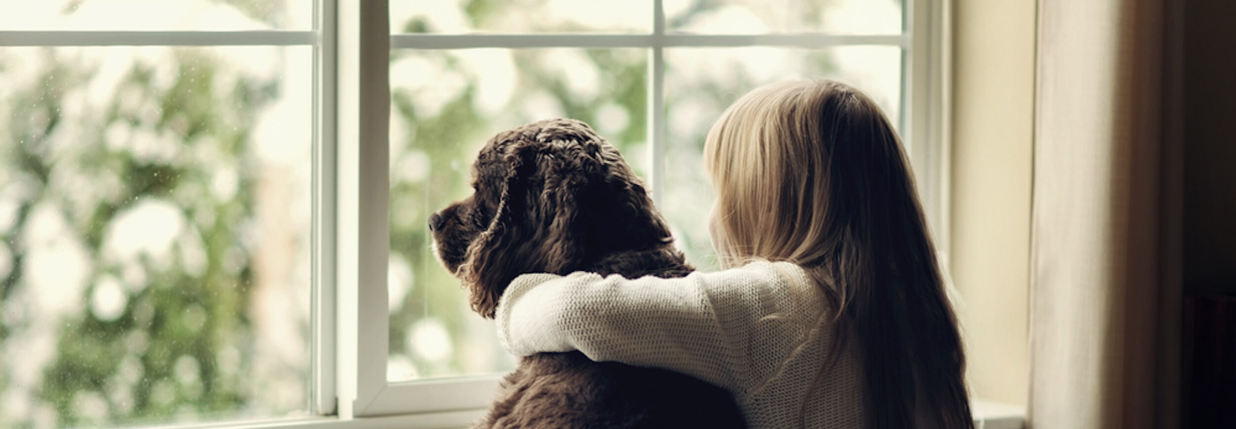 Girl Sitting Next To Dog While Looking Out The Window In Winter