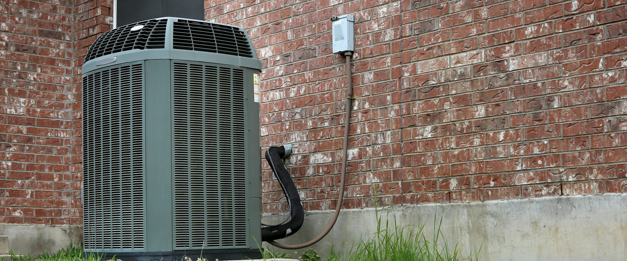 Heat Pump In Green Grass Outside Of Home